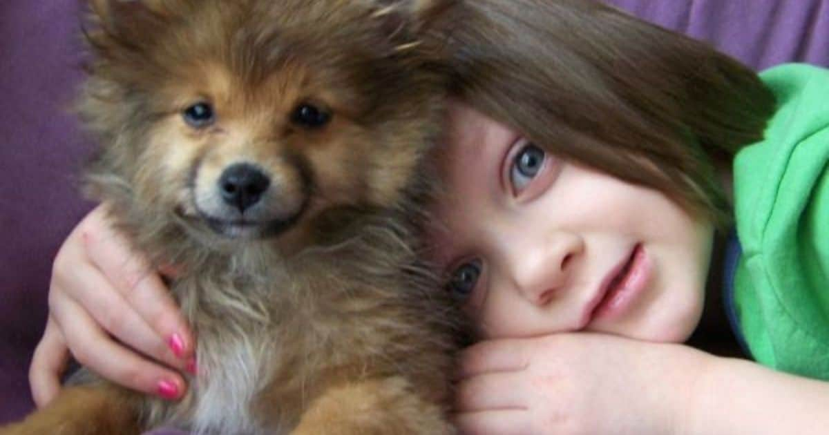 child snuggling with dog